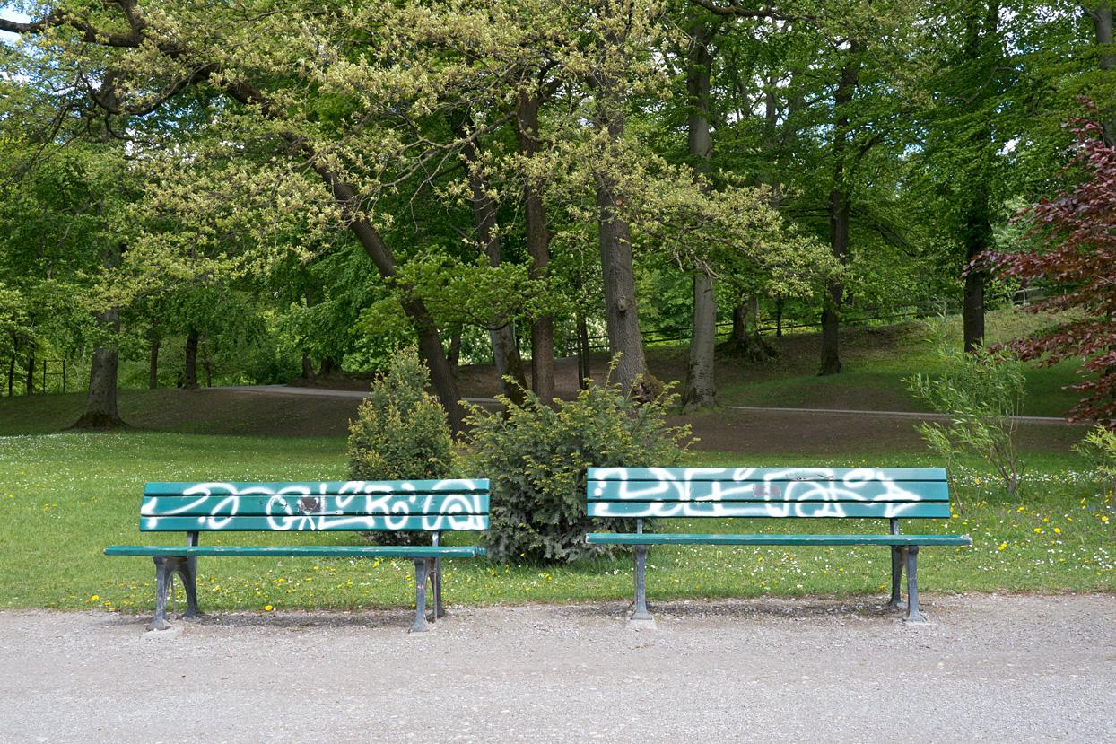 Zwei leere Parkbänke mit Graffitis
