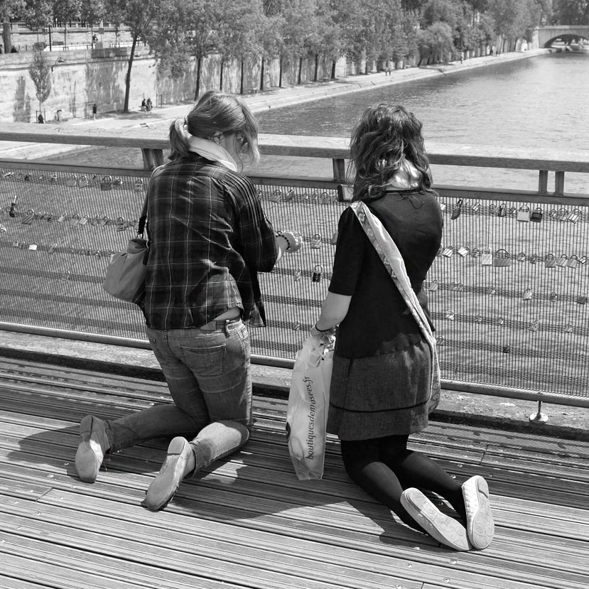 Zwei junge Frauen hängen Liebesschloss an ein Brückengeländer