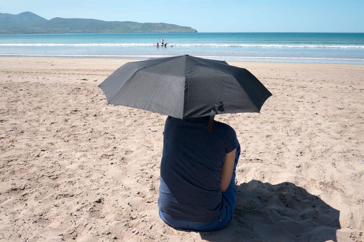 Frau mit Regenschirm am Strand