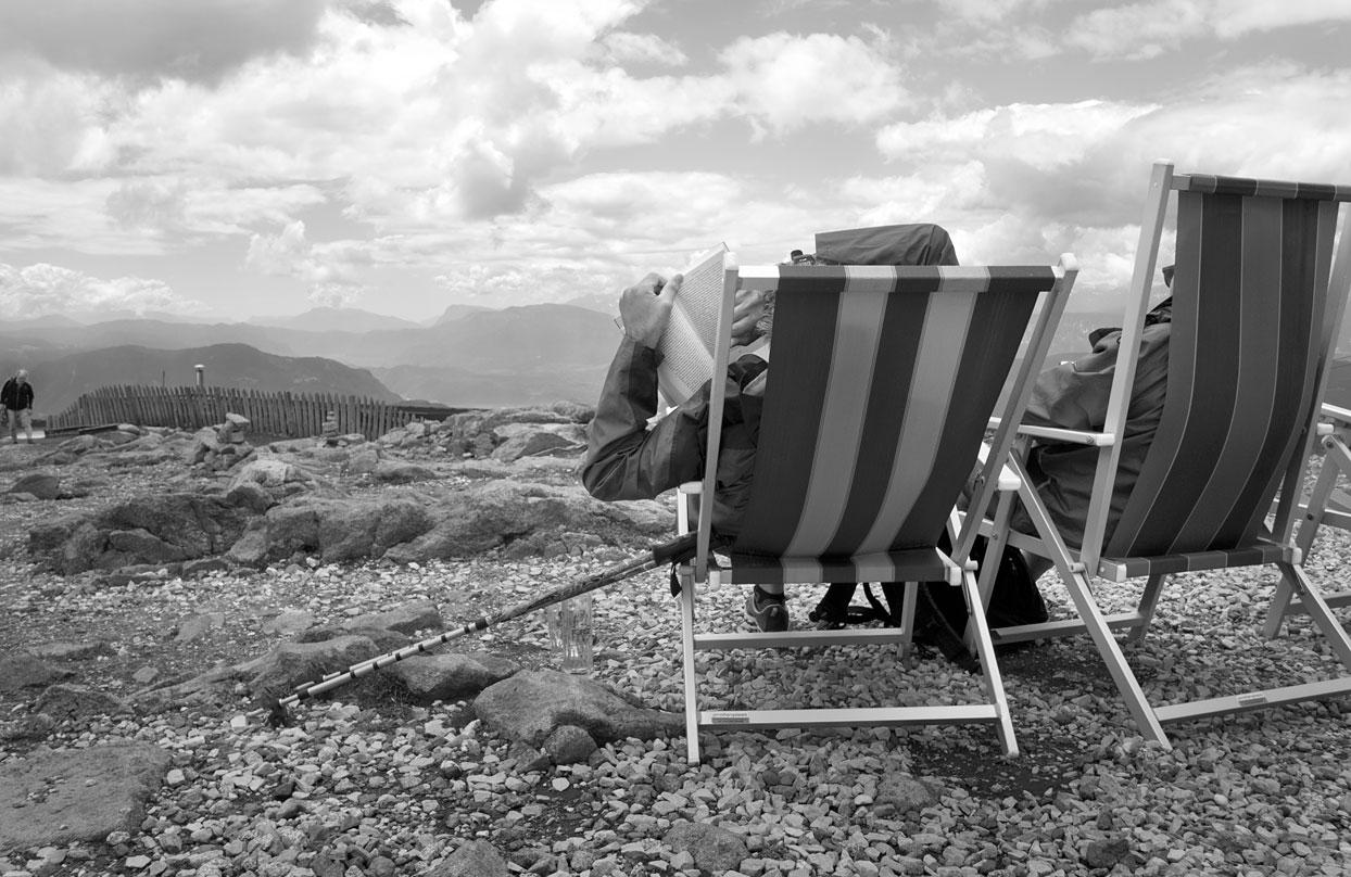 Lesender in Liegestuhl auf Berggipfel