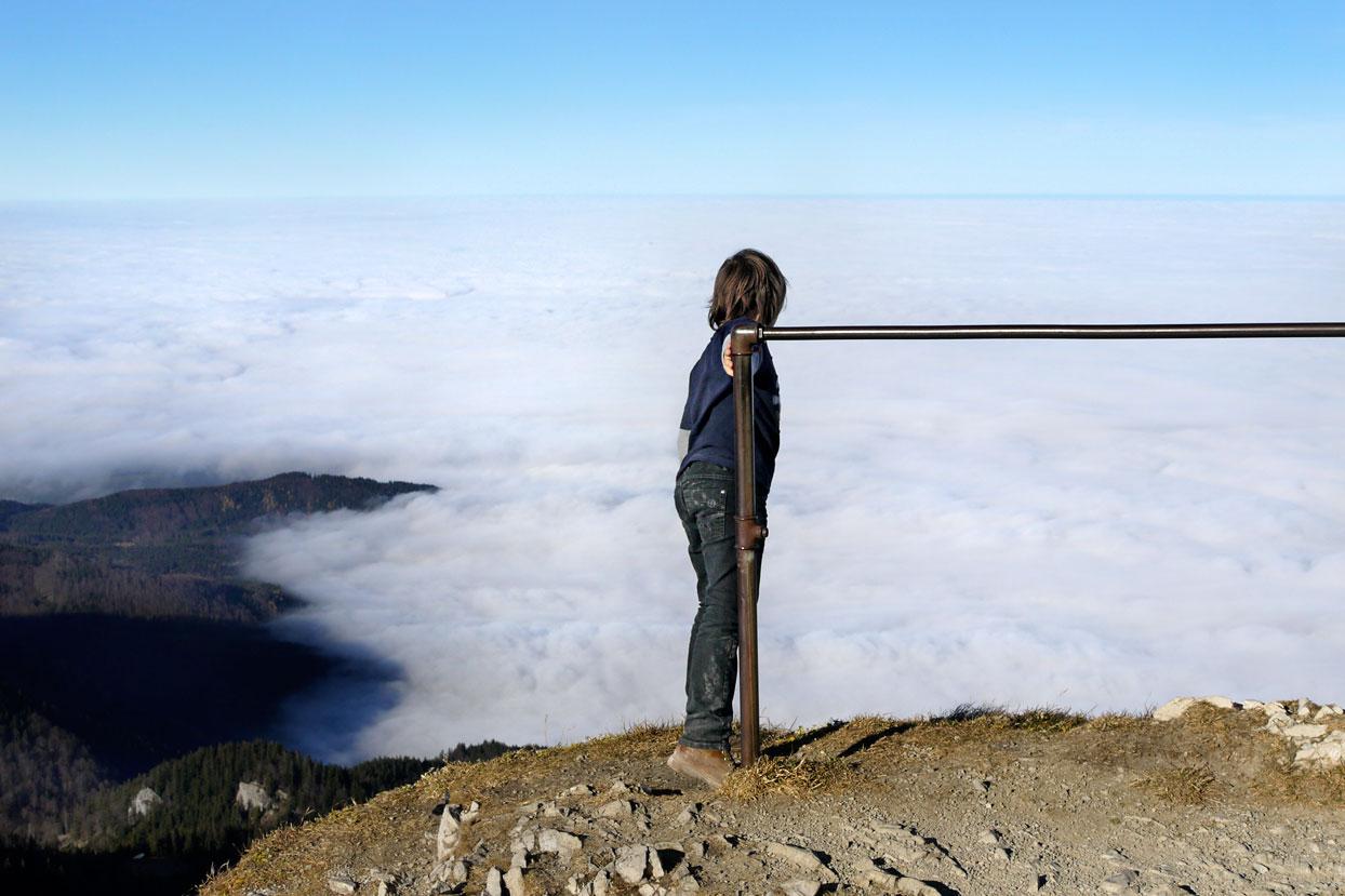 Junge auf Berggipfel über Wolkenmeer