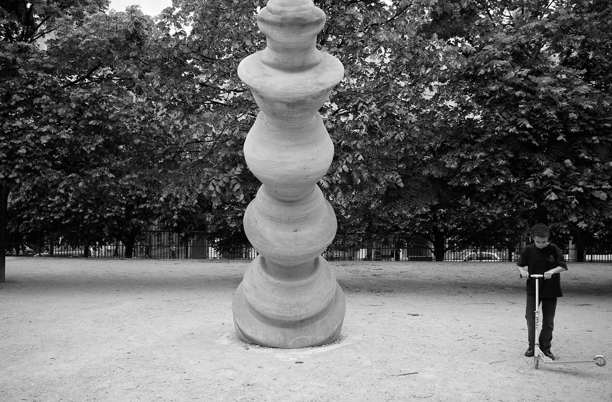 Skulptur in Park mit Junge und Tretroller