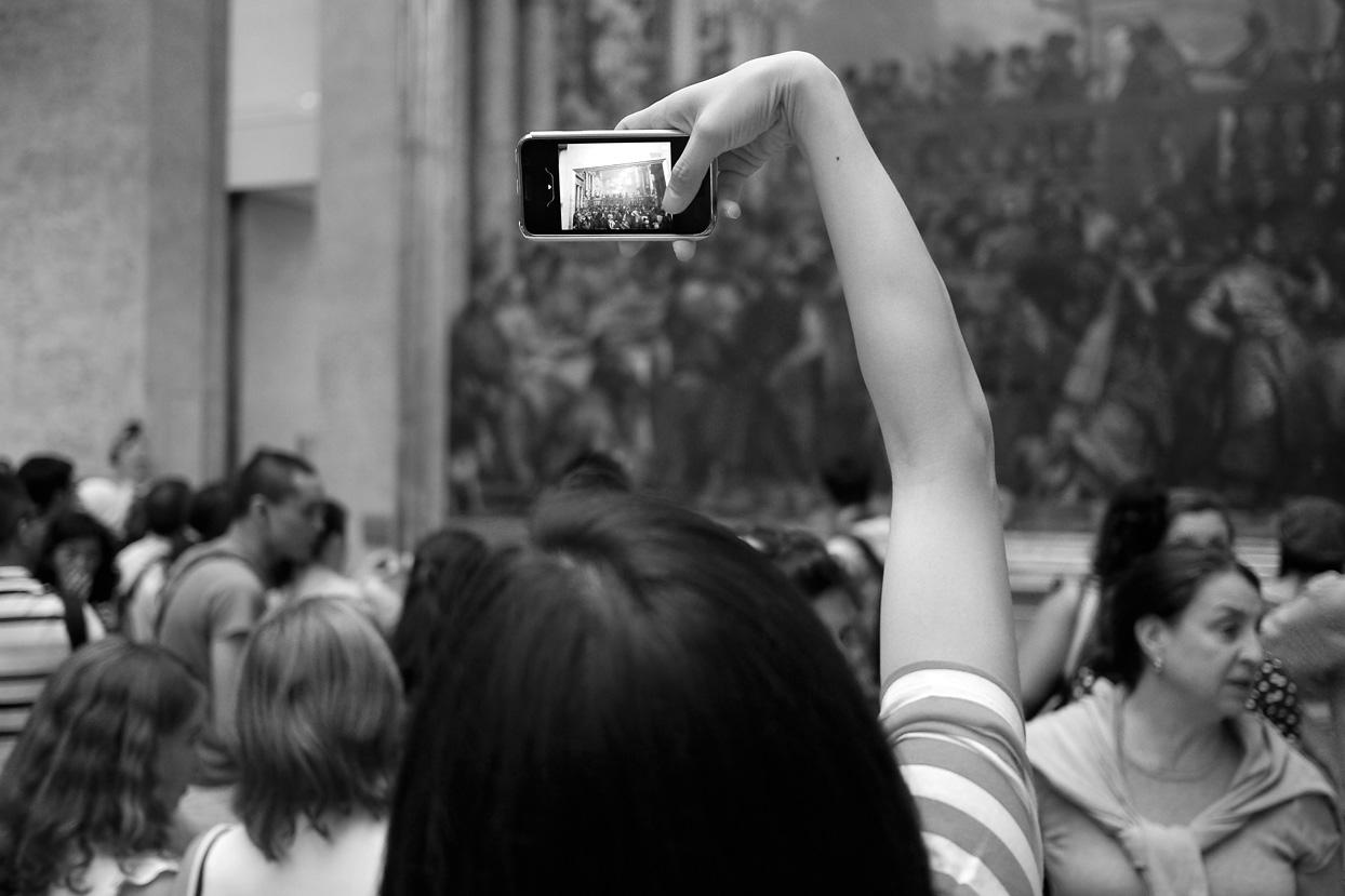Frau fotografiert Gemälde mit Handy