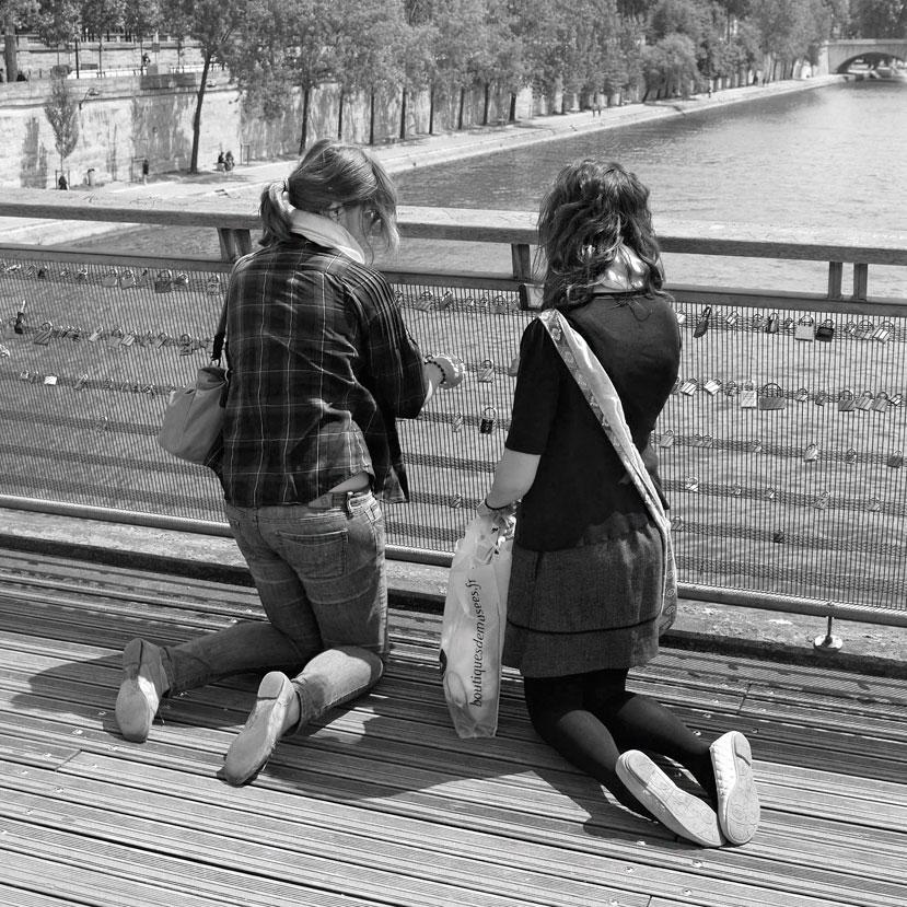 Zwei junge Frauen hängen ein Liebesschloss an ein Brückengeländer