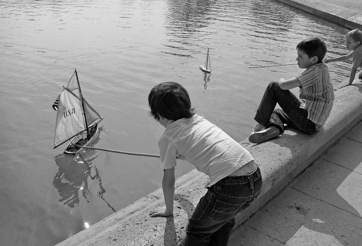 Jungen spielen mit Modell-Segelbooten